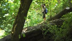 Boy walks out on log and looks through binoculars - stock footage