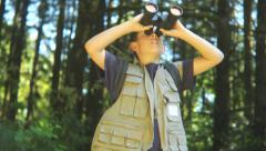 Young boy in forest looking through binoculars - stock footage
