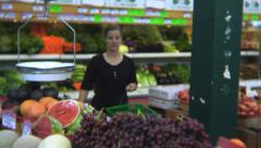 Woman looking at produce in the grocery store Stock Footage