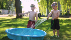 Two young boys playing in a pool in the garden - stock footage