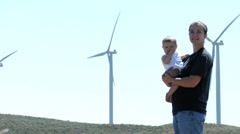 Mother and baby stand in a field of wind turbines - stock footage