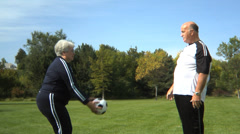 Senior couple playing with ball at park - stock footage
