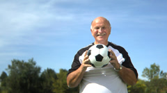 Senior man at park playing with soccer ball - stock footage
