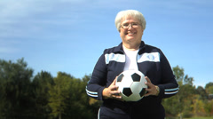 Portrait of elderly woman with a ball in the park - stock footage