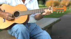 Portrait of elderly man playing guitar in the park Stock Footage