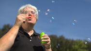 Stock Video Footage of Elderly woman blowing bubbles in the park