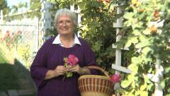 Portrait of senior woman in garden with rose - stock footage