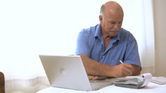 Senior man works on personal finances - stock footage