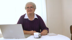 Portrait of senior woman with laptop and calculator - stock footage