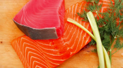 Salmon and red tuna fish pieces over wood Stock Footage