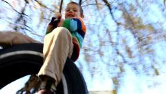Young boy swinging on tire swing Stock Footage