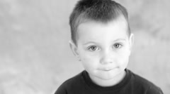 Young boy against black and white background Stock Footage
