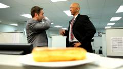 Two businessmen in office race to get last doughnut Stock Footage