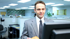 Businessman eating a doughnut and making mess - stock footage