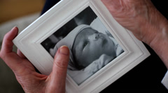 Grandmother holds framed photo of baby - stock footage