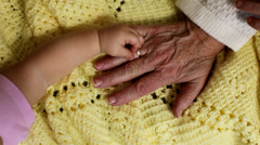 Close up of baby and grandma's hands Stock Footage