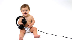 Baby girl with headphones against white background Stock Footage