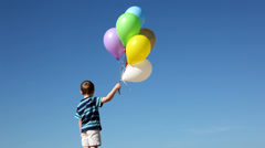 Boy lets balloon go into sky - stock footage