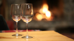 Pouring glasses of wine by fireplace Stock Footage