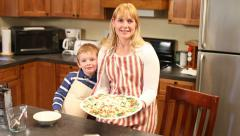 Woman and young son in kitchen with pizza Stock Footage