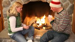 Couple playing cards by fireplace - stock footage