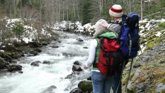Backpackers standing by river throwing rocks Stock Footage