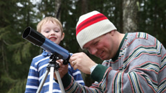 Father and son looking through telescope Stock Footage