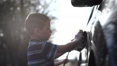 Young boy washing car Stock Footage