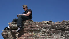 Young man using mobile phone on cliff Stock Footage