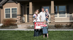 Happy family in front of their new house Stock Footage