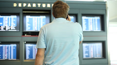 Man at airport in front of departure screens Stock Footage