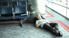 Young man sleeping at airport - stock footage