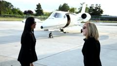 Business women meet in front of jet - stock footage