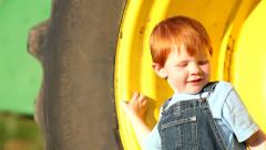Editorial: Young boy climbs into tractor wheel Stock Footage
