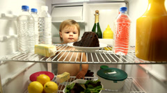 Baby eating chocolate cake in refrigerator Stock Footage