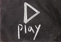 Play sign drawn with chalk on blackboard Stock Photos