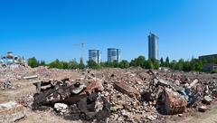 pile of debris of ruined building on new buildings background - stock photo