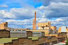 Large factory with smoking chimneys against the blue sky Stock Photos