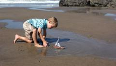 Young boy at beach playing with toy boat Stock Footage