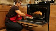 Stock Video Footage of Woman gets Thanksgiving turkey out of oven