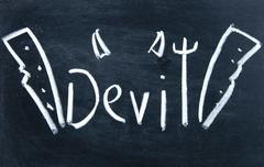 Devil sign drawn with chalk on blackboard Stock Photos
