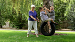 Woman pushing grandchildren on swing Stock Footage