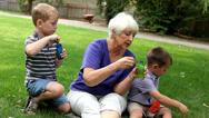 Stock Video Footage of Senior woman and two young boys blowing bubbles