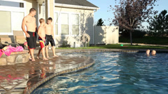 Big brother throws little brothers in pool - stock footage