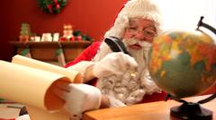 Santa Claus looking at antique globe Stock Footage