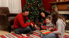 Family by Christmas tree playing with toys - stock footage