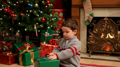 Young boy opening a Christmas present Stock Footage