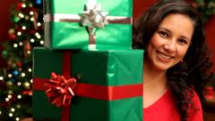 Woman looking out from behind Christmas gifts Stock Footage