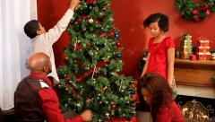 Family decorating Christmas tree together - stock footage