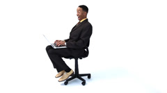 Happy businessman spinning in chair with laptop - stock footage